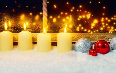 Vier Kerzen und Kugeln am Fenster