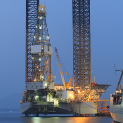 Jack up oil drilling rig in the shipyard in the evening