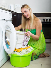 girl in green dress using washing machine