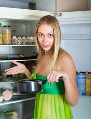 Woman holding foul food near fridge