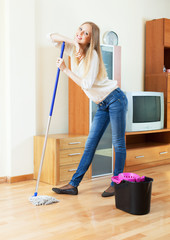 Positive long-haired girl washing parquet  with mop