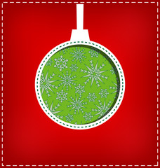 Green Christmas ball cutout on red background