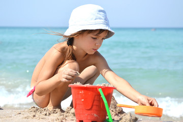 Little girl playing with sand on the sea shore