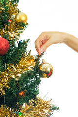 Girl's hand decorating the Christmas tree with baubles
