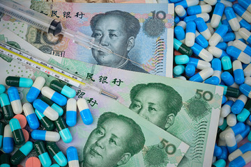 thermometer,syringe and pills  on Yuan banknotes for health conc