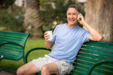 Fifties male on the phone in the park with coffee