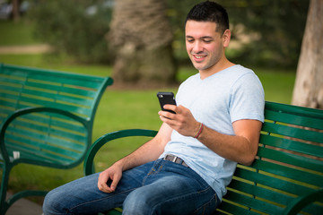 Young guy using his phone at the park