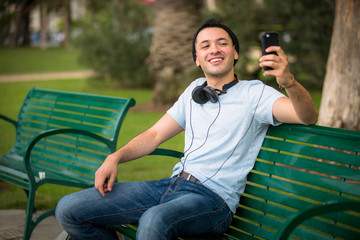 Young hip male taking a selfie at the park