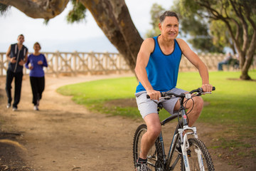 Male riding his bicycle while others run