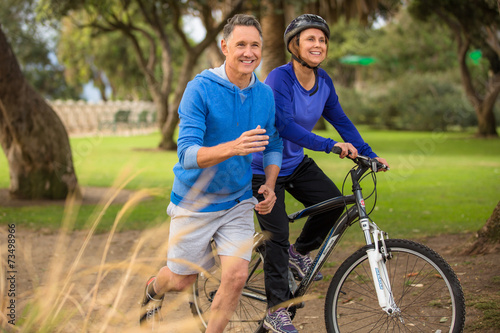 Elder couple exercising in the park - 73498966