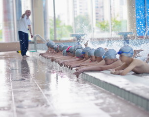 group of happy kids children at swimming pool class learning to