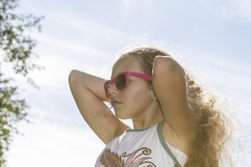 Young girl fixing her sunlit long blond hair.
