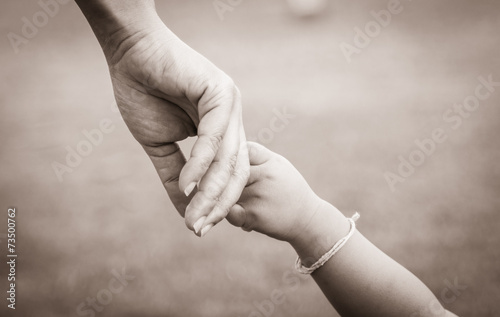 hands of mother and child - 73500762