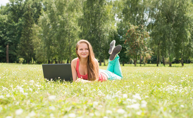 Happy student on grass with laptop. Girl outdoor using pc.