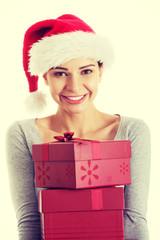 Beautifull woman in santa hat holding presents.
