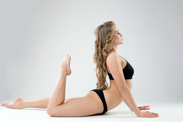Side view of beautiful woman exercising pilates