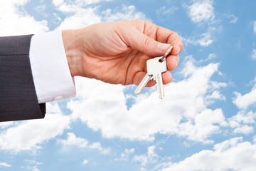 Real Estate Agent's Hand Holding Keys Against Cloudy Sky