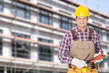 Architect Holding Adjustable Wrench Against Building