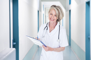 Female Doctor Writing Notes In Hospital Corridor