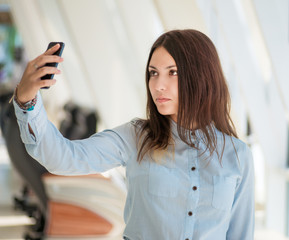 Young woman making selfie photo with her smartphone.