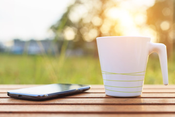 Coffee cup and smartphone on the table in sunset time