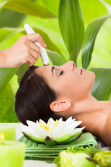 Woman Receiving Microdermabrasion Therapy Against Leaves
