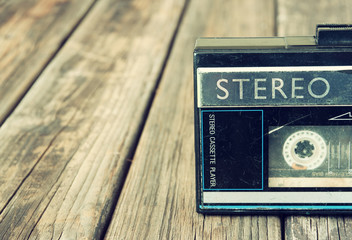 Old portable cassette player on a wooden background. image is in