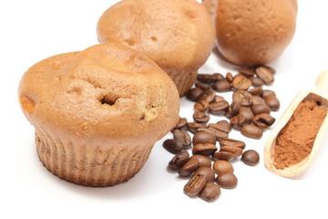 Fresh baked muffins, coffee grains and powdery cinnamon