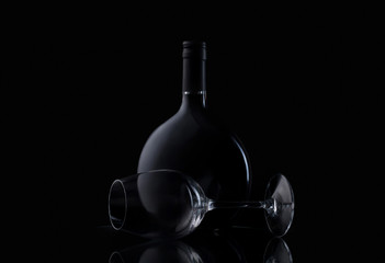 Bottle and glass of wine on black background