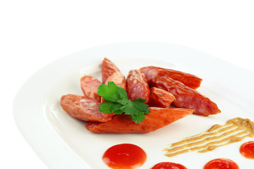 Smoked thin sausages and vegetables on plate, isolated on white