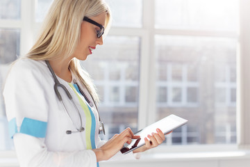 Female doctor looking at medical records on tablet computer