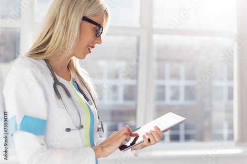 Female doctor looking at medical records on tablet computer плакат