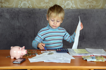 little boy is engaged in home accounting