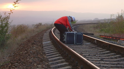 Tired passenger with suitcases sitting on railroad track