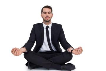 Peaceful businessman sitting in lotus pose relaxing
