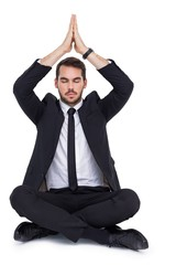 Businessman sitting in lotus pose with hands together