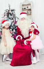 Saint Nicolas  and little girls near Christmas fir-tree
