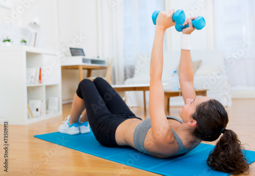 canvas print picture Young attractive girl doing exercise at home