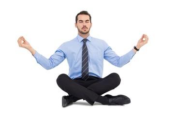 Calm businessman sitting in lotus pose