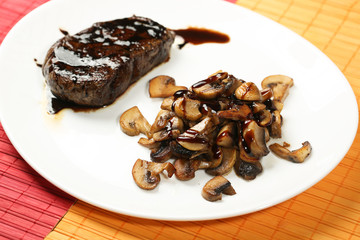 Meat slice with black sauce and mushrooms