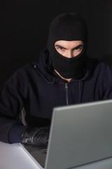 Burglar sitting hacking laptop while looking at camera
