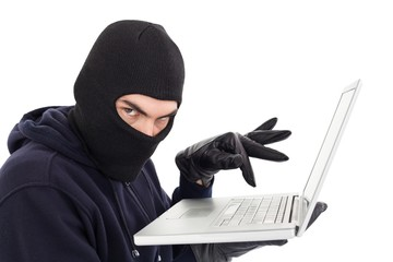 Hacker in balaclava standing and typing on laptop