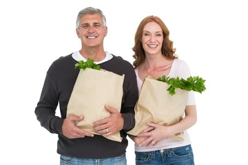 Casual couple holding grocery bags