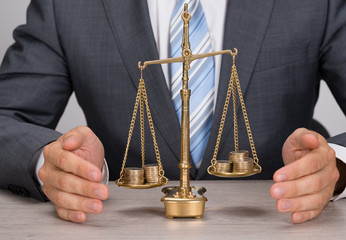 Businessman Protecting Justice Scale With Coins