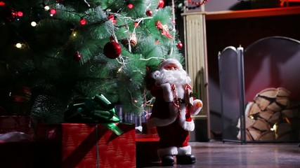 Santa Claus beside a  Christmas tree