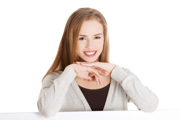 Blond woman with hand on chin sitting at the desk