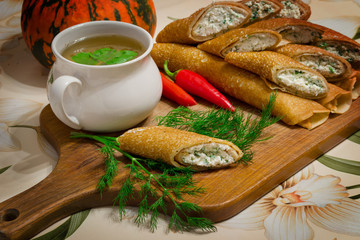 cup of soup and pancakes, rolled on a wooden board with herbs an