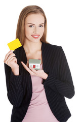 Businesswoman holding house model and yellow card