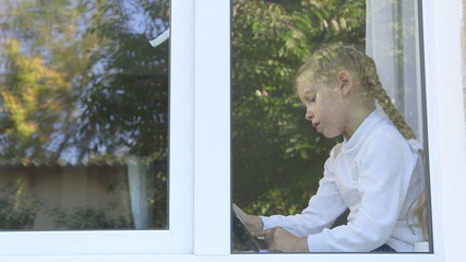 Cute little girl by window playing  digital tablet