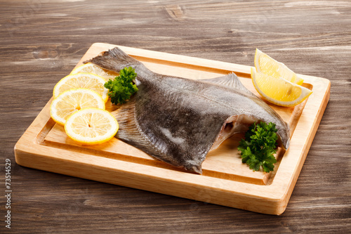 Fototapeta Fresh raw flounder on cutting board